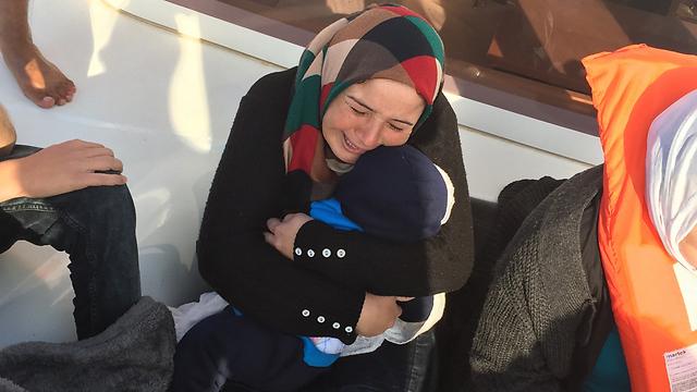szíriai nő halott csecsemőjével a kezében