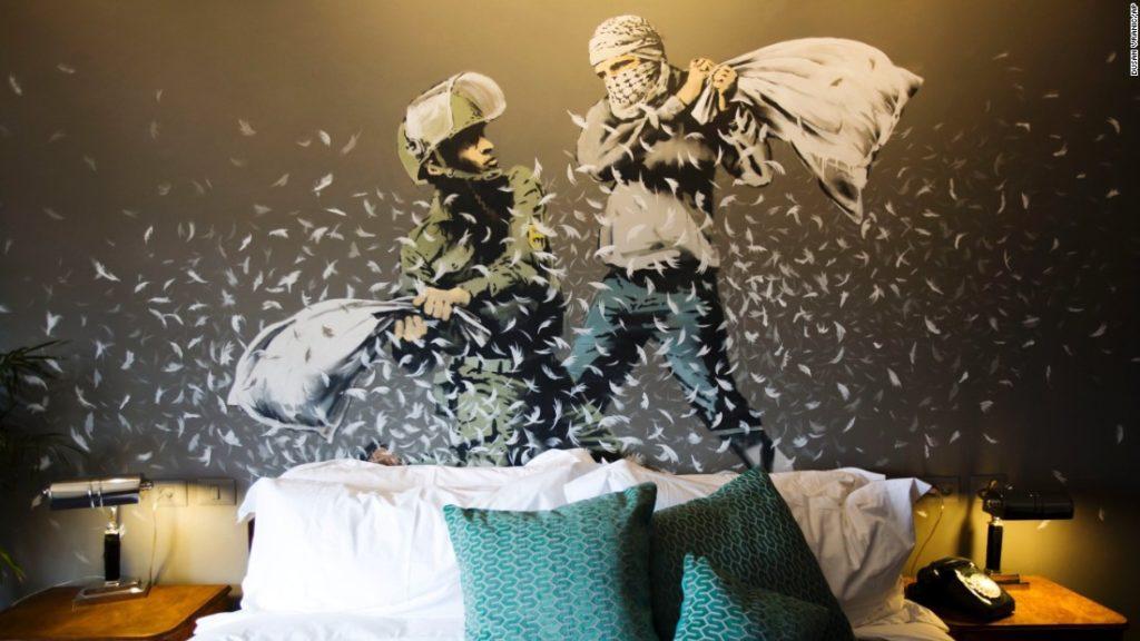 Izraeli katona palesztin tüntetővel párnacsatázik egy betlehemi szálloda falán