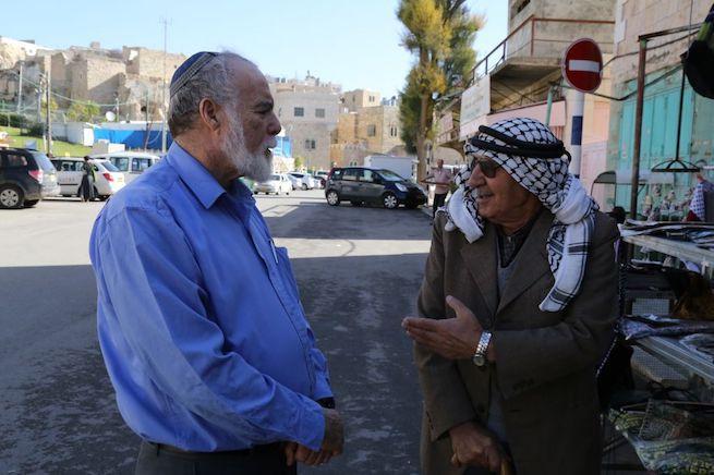 Egy izraeli és egy palesztin férfi beszélgetnek Hebronban