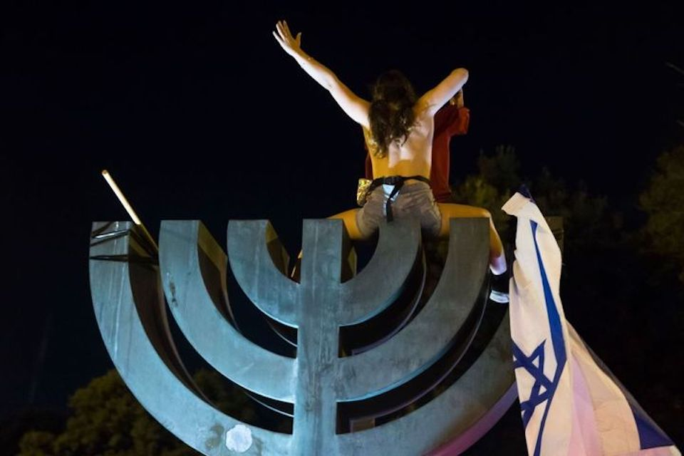 Félmeztelenül demonstrált egy nő az izraeli parlament melletti menóra tetején
